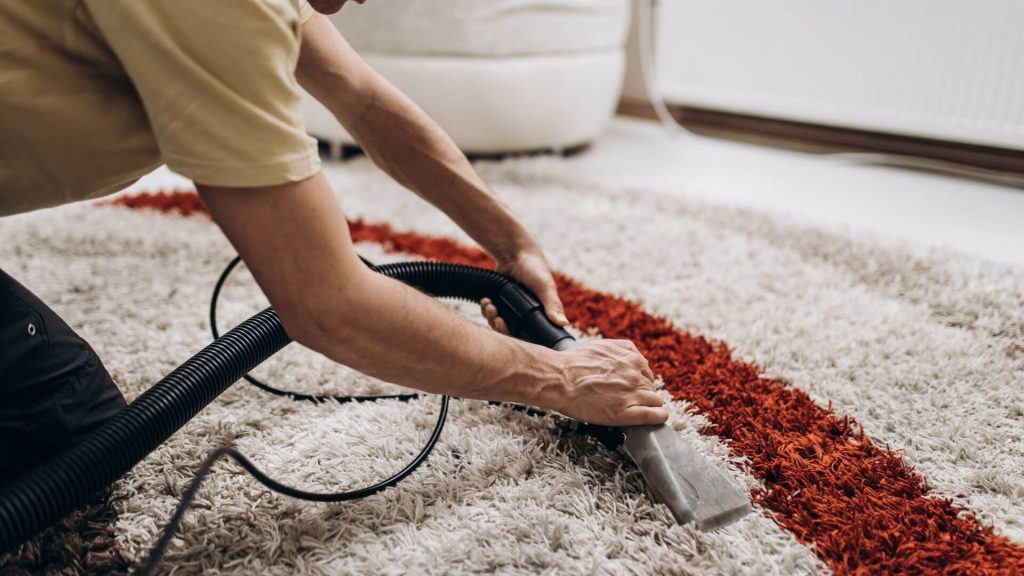 a picture of a man scrubbing clean a carpet