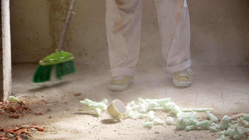 a man sweeping the dusty floor of a construction site
