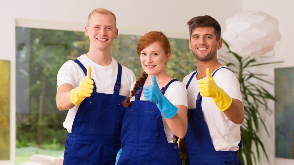 three cleaners posing and doing thumbs up with their cleaning attire on.