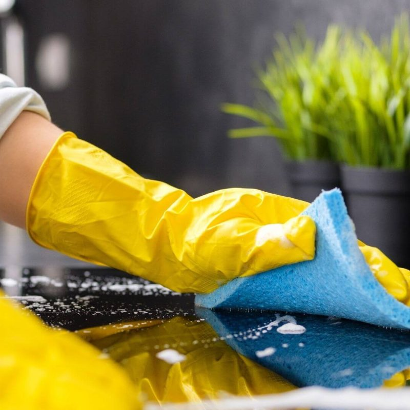two hands wearing yellow gloves wiping and cleaning a table surface