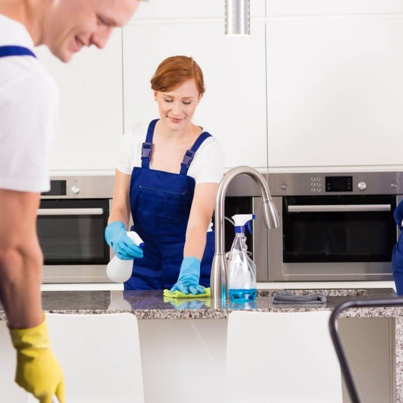 three people cleaning a kitchen